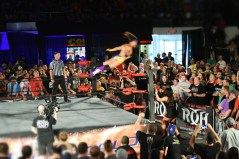Matt Tavin leaping from the ring before crushing Jay Lethal against the guardrail