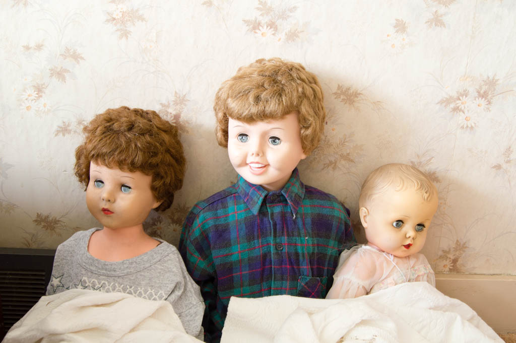 Three dolls inside the abandoned house of toys