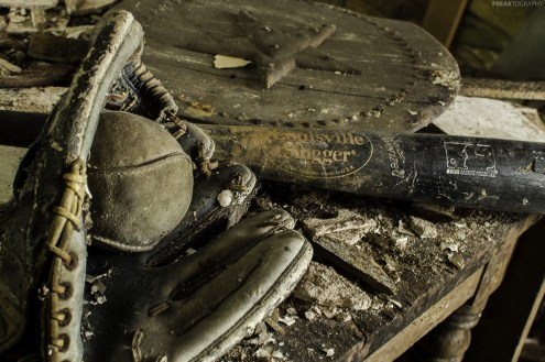 A very well used baseball glove and well worn Louisville Slugger. These items were found in different parts of the house and placed together for this photograph in an abandoned house.