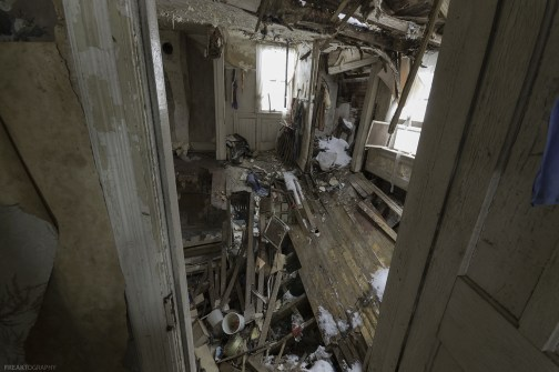 The second level of this abandoned house has crashed into the main floor and the main floor has crashed into the basement.