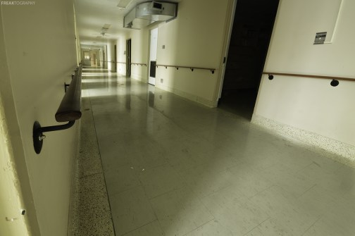 A hallway in the geriatric ward of a vacant psychiatric hospital.
