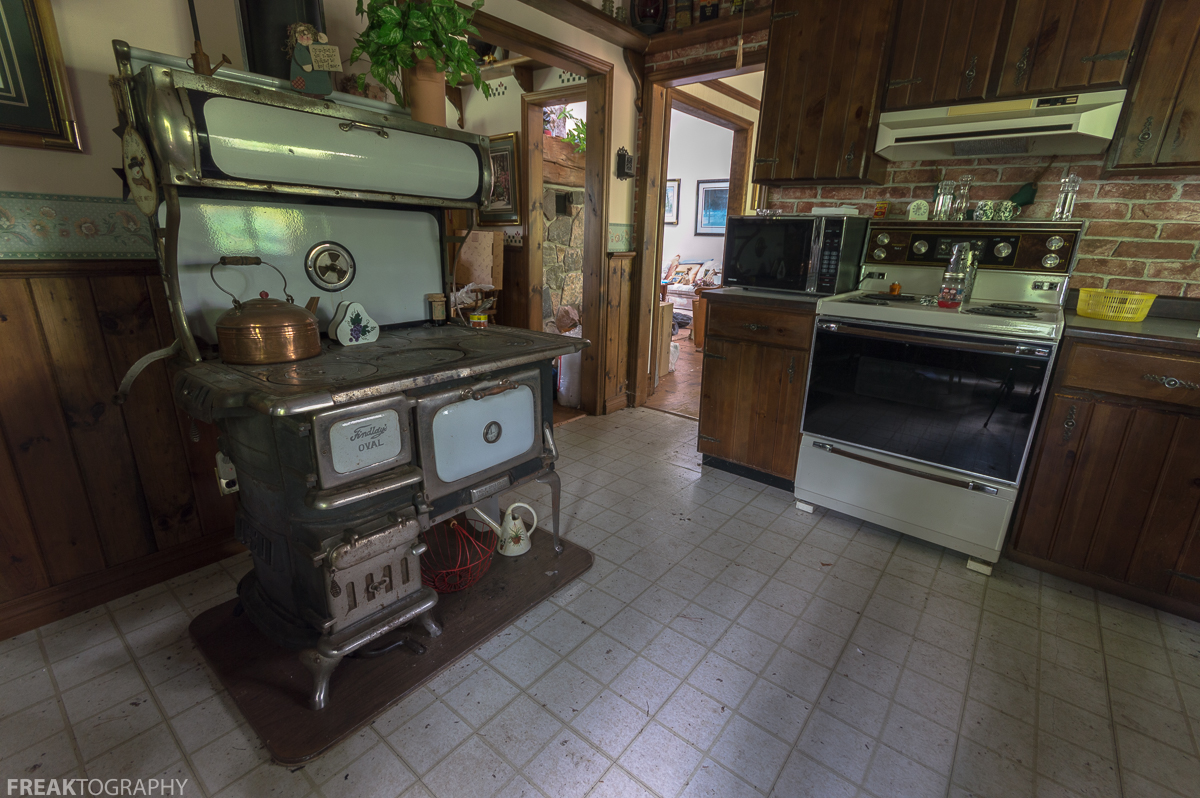 An Antique Findlays Oval Wood Burning Cook Stove Beside A Modern Ish And Microwave Found In The Kitchen Of This Abandoned Time Capsule House