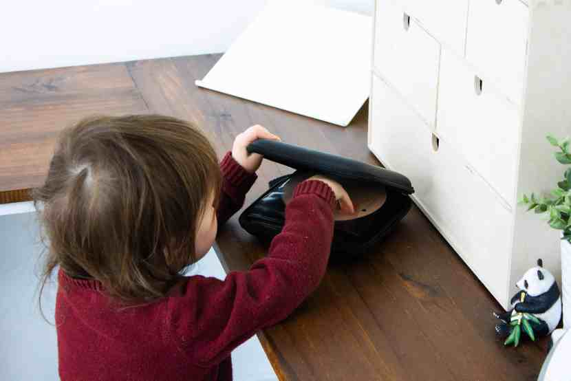 Toddler accessing music CDs from a small case in a Montessori home