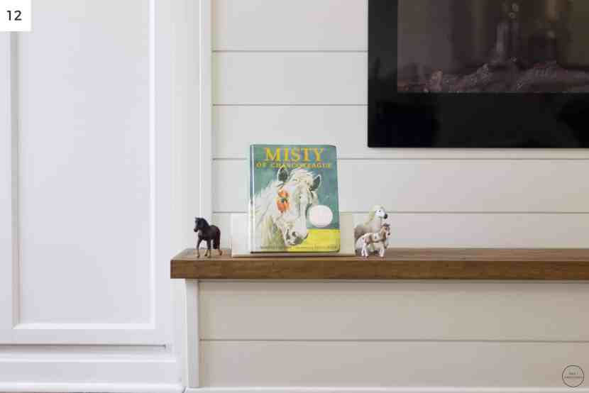the wooden hearth provides a nice, level surface to store toys and books for kids