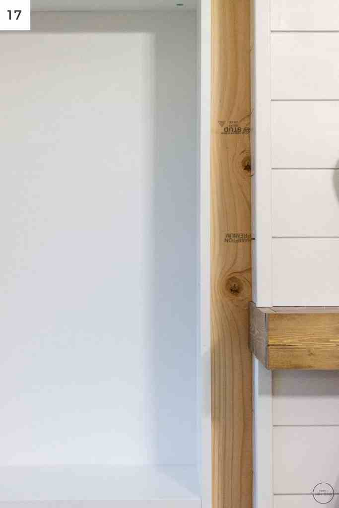 a 2x4 is used to space the IKEA Billy bookcases an even distance away from the electric fireplace surround