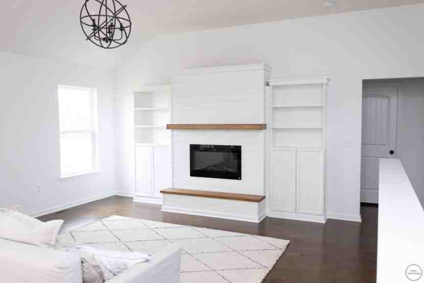 living room featuring a modern farmhouse shiplap electric fireplace and built-in Billy bookcases from IKEA