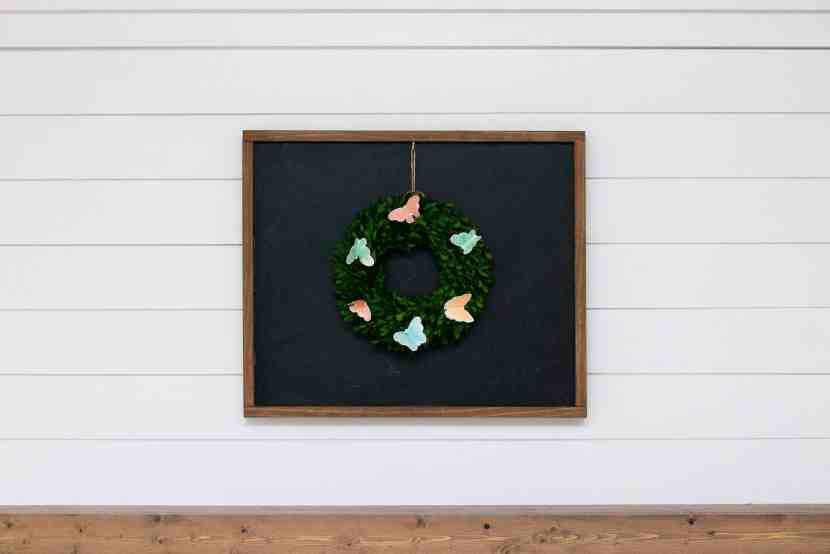 wooden framed chalkboard with butterfly wreath sitting above a wooden floating mantle