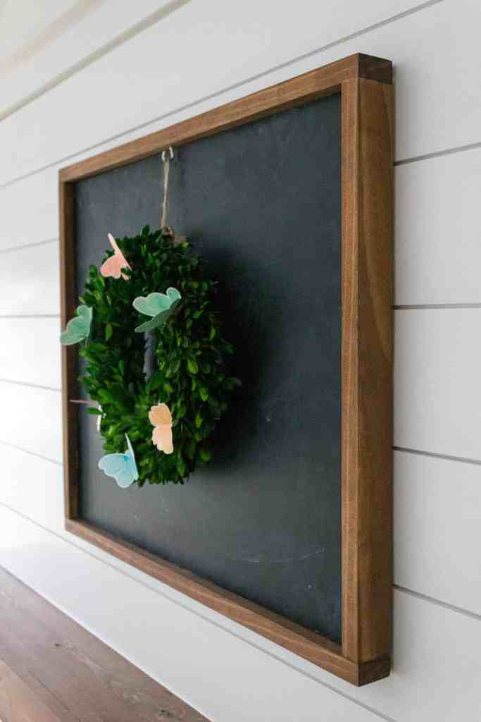 wooden framed chalkboard hanging on shiplap surround above a floating wooden mantle