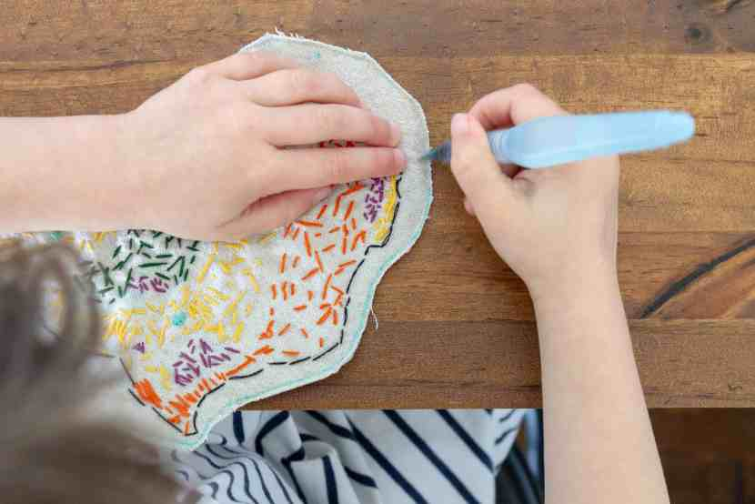 The embroidered map of the biomes of Africa has been sewn and cut out. A young girl now uses a water brush to erase the last fabric market template lines.