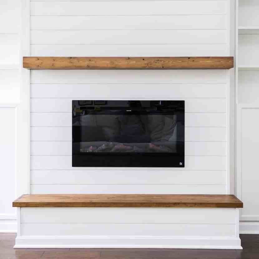 Modern farmhouse electric fireplace with floating mantle and wooden hearth.