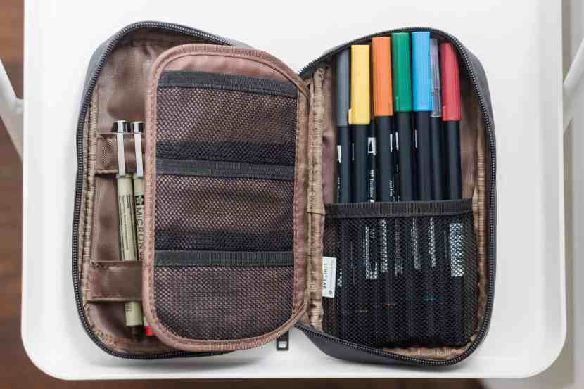 Micron pens and Tombow markers are neatly stored inside a travel case.