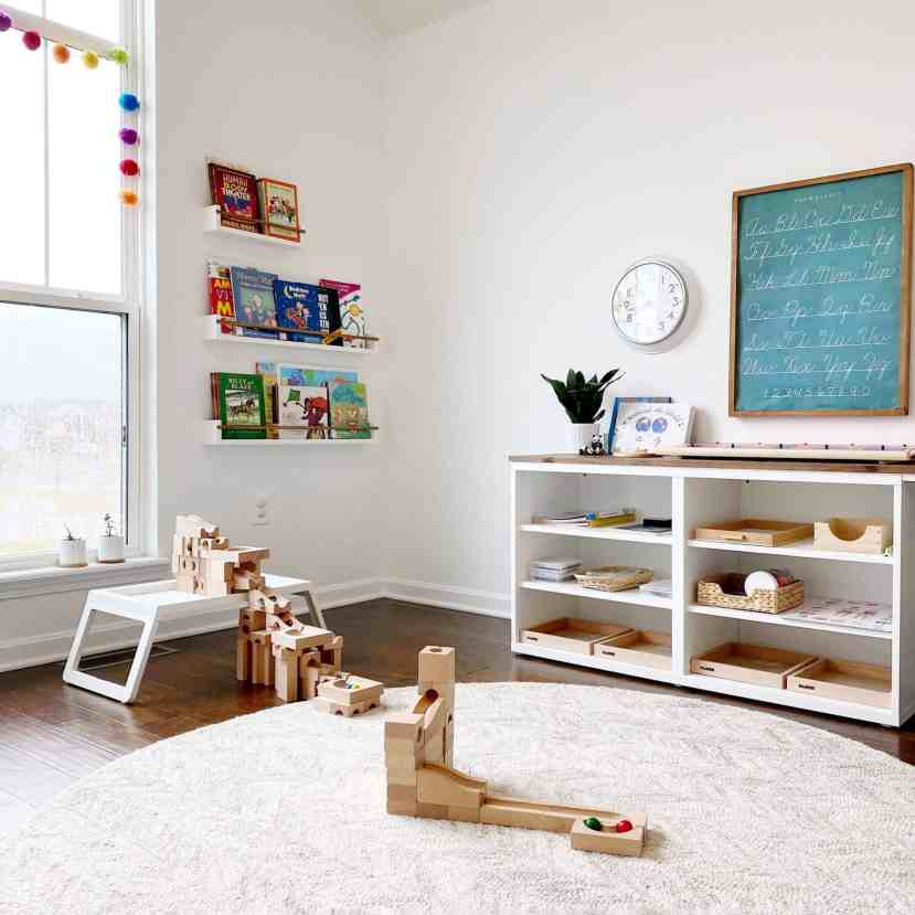 A Montessori-inspired homeschool room with a Kaden marble run and modern, minimalist floating bookshelves displaying books forward-facing to engage children's attention. #booknook #raisingreaders #montessori #montessoriathome #homeschoolroom #earlyliteracy #bookdisplay