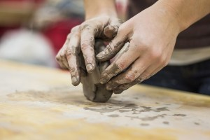 person sculpting clay with their hands on a wooden table
