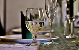 glass of wine on dinner table with fancy china symbolizes virtual meeting