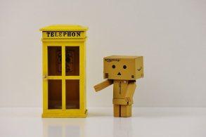 cardboard man standing beside telephone booth