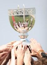soccer teammates holding up a trophy together