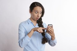 Women looking shocked at her smartphone feeling conference call anxiety