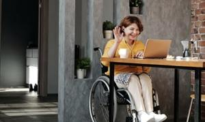 Woman in wheelchair sitting at table at home in front of open laptop, smiling and waving and chatting online