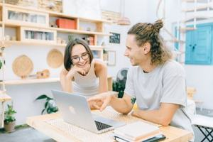 Young man and woman pointing and laughing sitting at table in at-home studio with books, pointing at open laptop