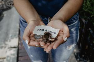 """View of woman's hands holding out coins at waist level with a little note saying, """"Make a change"""