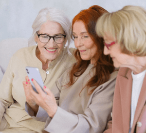 Direct view of three senior women seated together with middle woman holding a device and all three engaged, smiling and interacting with it-min