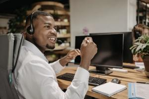 Side view of employee smiling and in mid-conversation, seated at desktop computer in office space with headphones, looking to the right