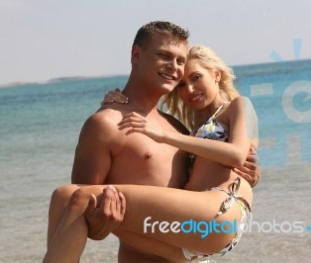 Man Holding Woman At Beach Stock Photo