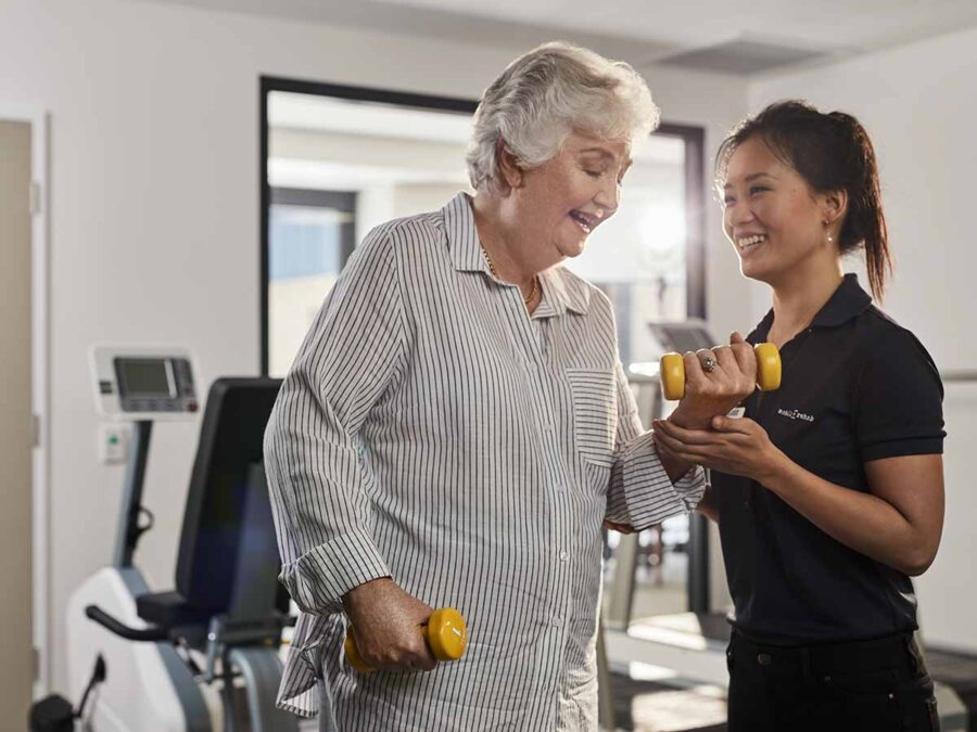 aveo_corporate_care_female resident doing weights with mobile rehab smiling_1200x900