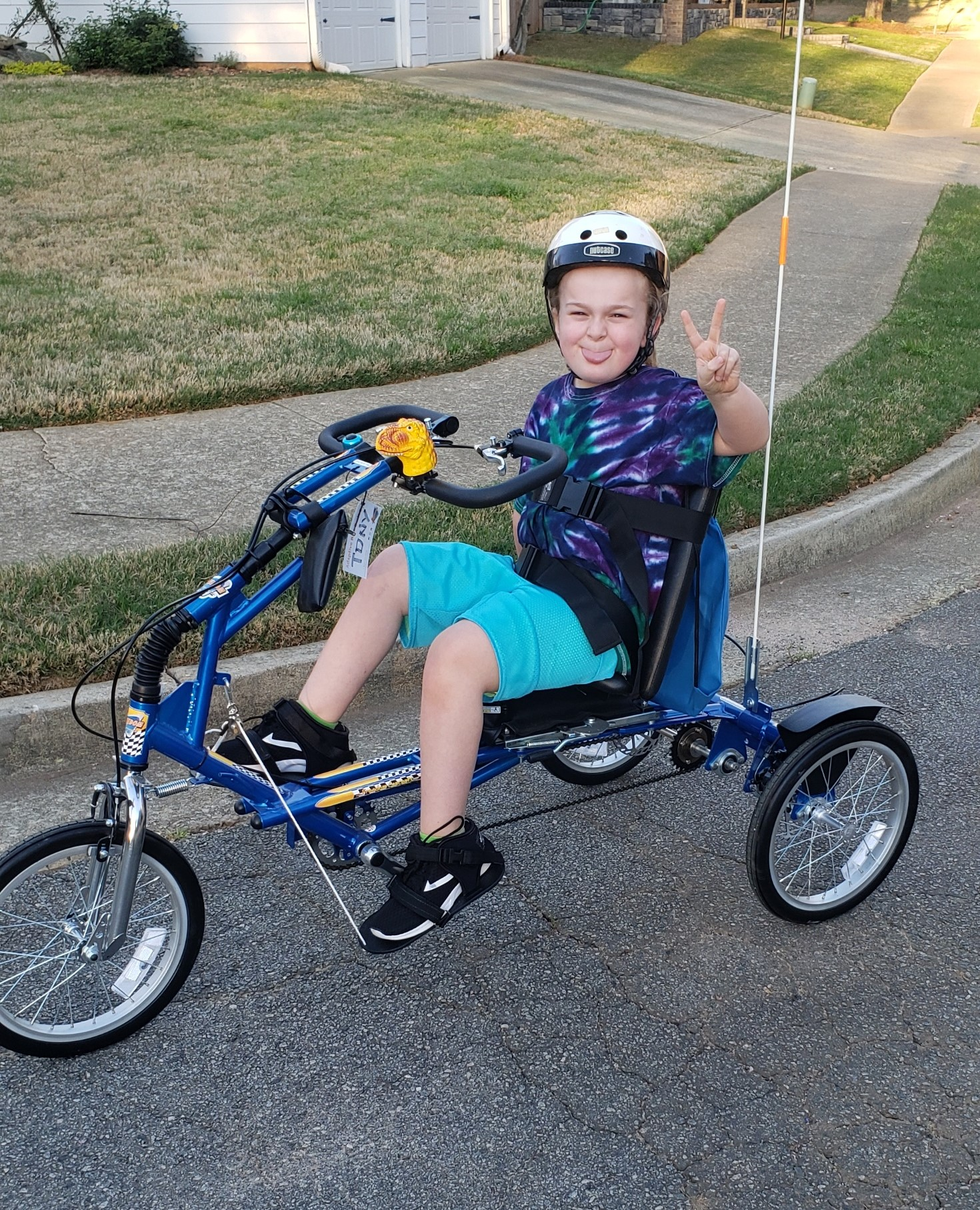 Ayden sitting on his adaptive bike making a peace sign with his hands.