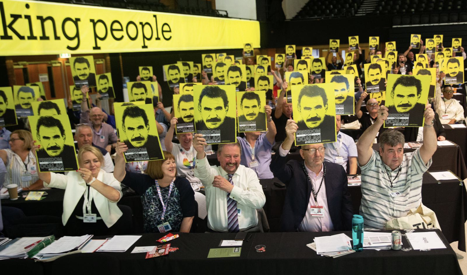 Senior trade unionists hold placards calling for Freedom for Ocalan at TUC 2019