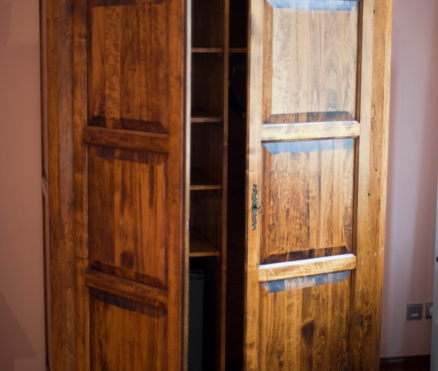 Rustic Wooden Wardrobe Or Armoire In A Bedroom With Its Double Doors Atnding Ajar To Reveal