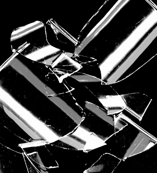 Free Stock Photo: Broken shards of glass reflecting light scattered in a random heap on a black background in a close up view