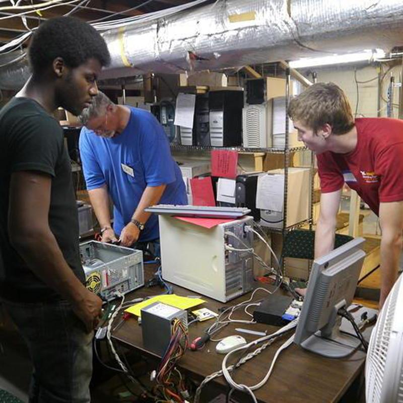 a group of volunteers refurbish computers
