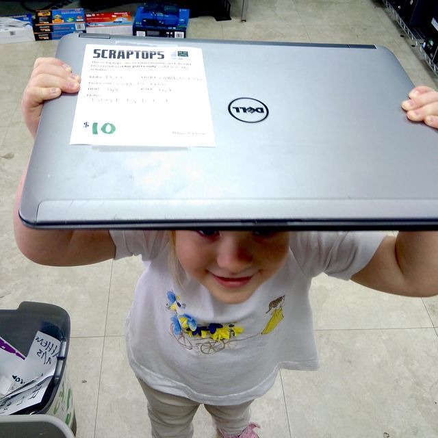a toddler holding up a laptop