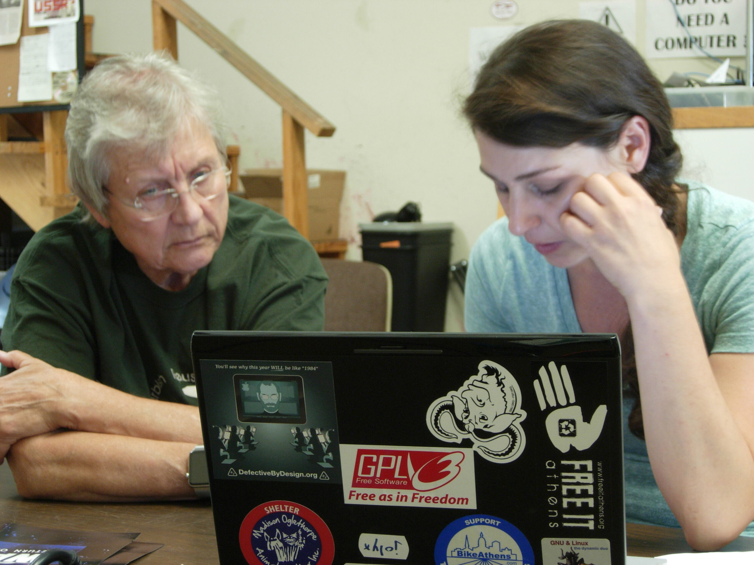two people work at a laptop with colorful stickers