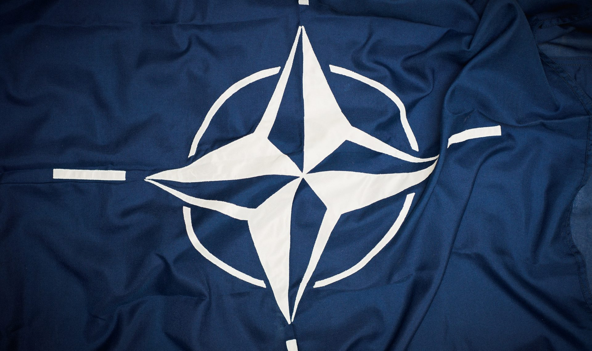 The flag of the North Atlantic Treaty Organization (NATO) consists of a dark blue field charged with a white compass rose emblem, with four white lines radiating from the four cardinal directions. Adopted three years after the creation of the organization, it has been the flag of NATO since October 14, 1953. The blue colour symbolizes the Atlantic Ocean, while the circle stands for unity.