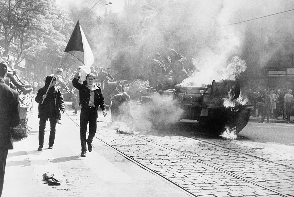 During the Soviet invasion of Czechoslovakia, Czechoslovaks carry their national flag past a burning tank in Prague, photo from CIA Analysis of the Warsaw Pact Forces