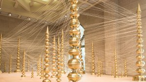 installation shot of tall gold spires arranged in clustsers and connected by white string