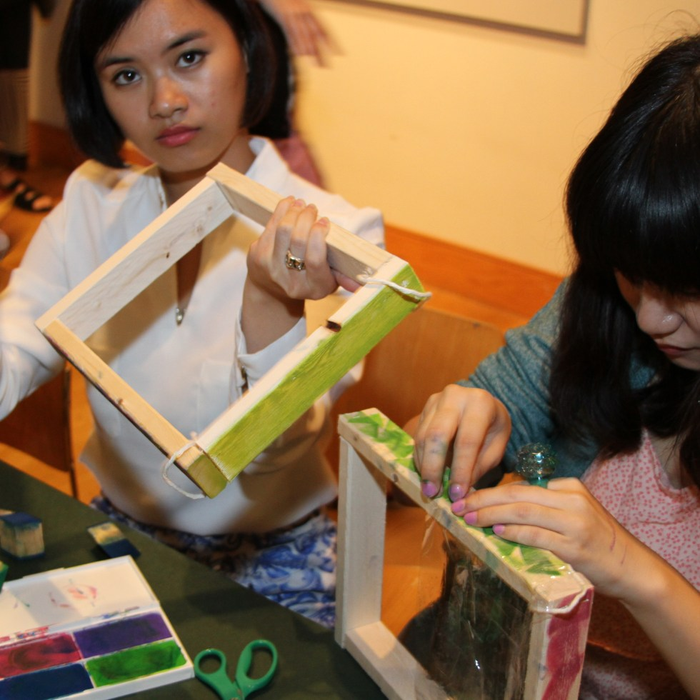 Two women sitting at a table, decorating frames.
