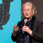 Dame Professor Jessica Rawson  holding a microphone