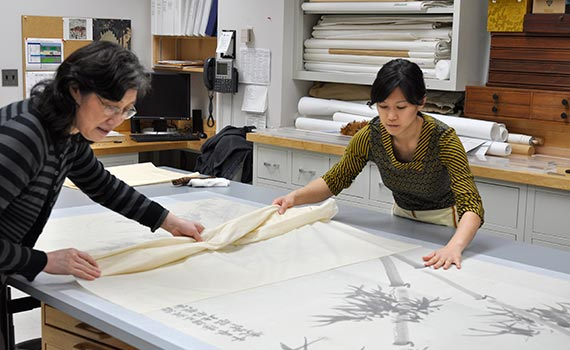 Grace Jan working alongside senior conservator Xiangmei Gu at the Freer|Sackler