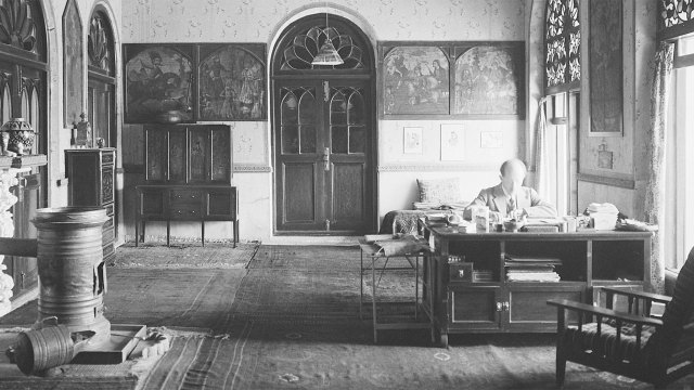 Black and white photo of Ernst Herzfeld in a sunlit room, decorated with many paintings, ceramics, and rugs, in his home, working at a desk.