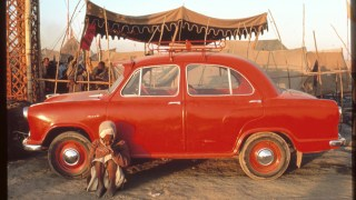 Red car with man seated on ground in front, tents in background.