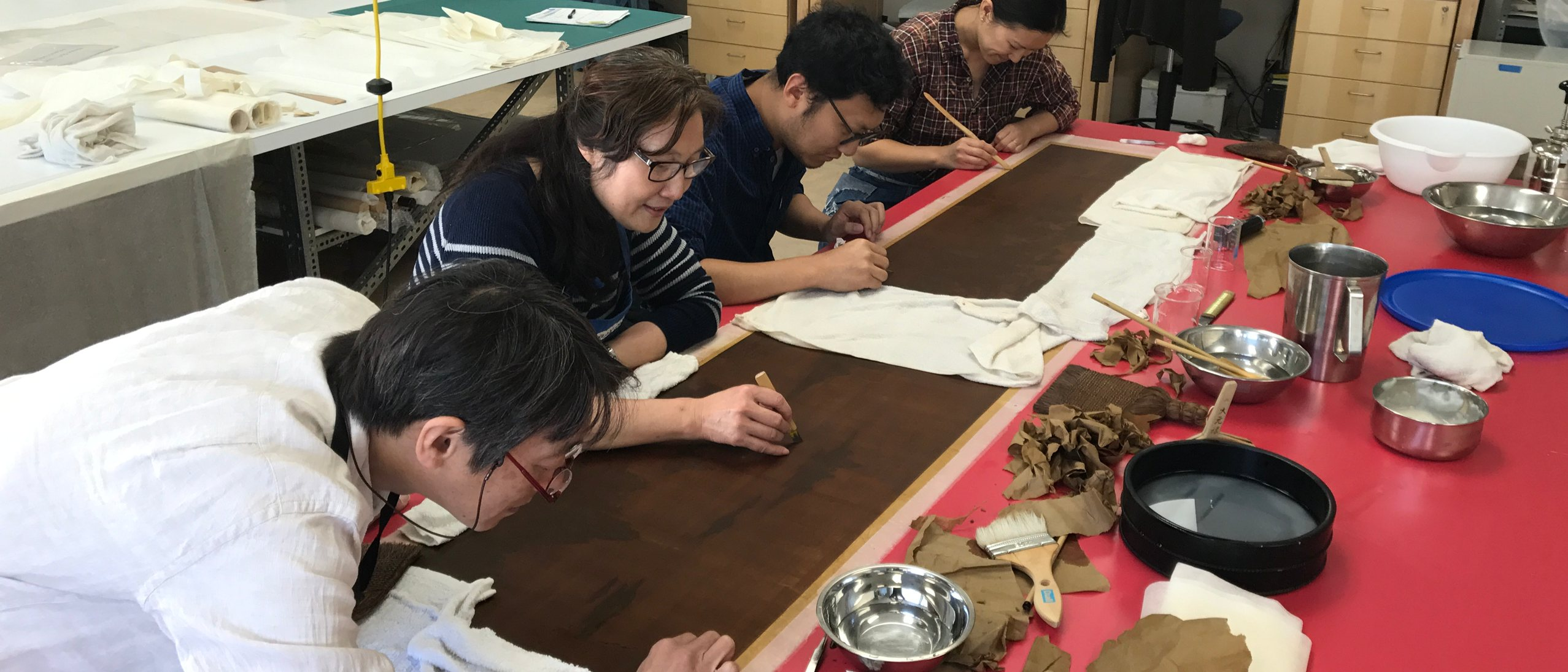 a team of four people working on paper scrolls
