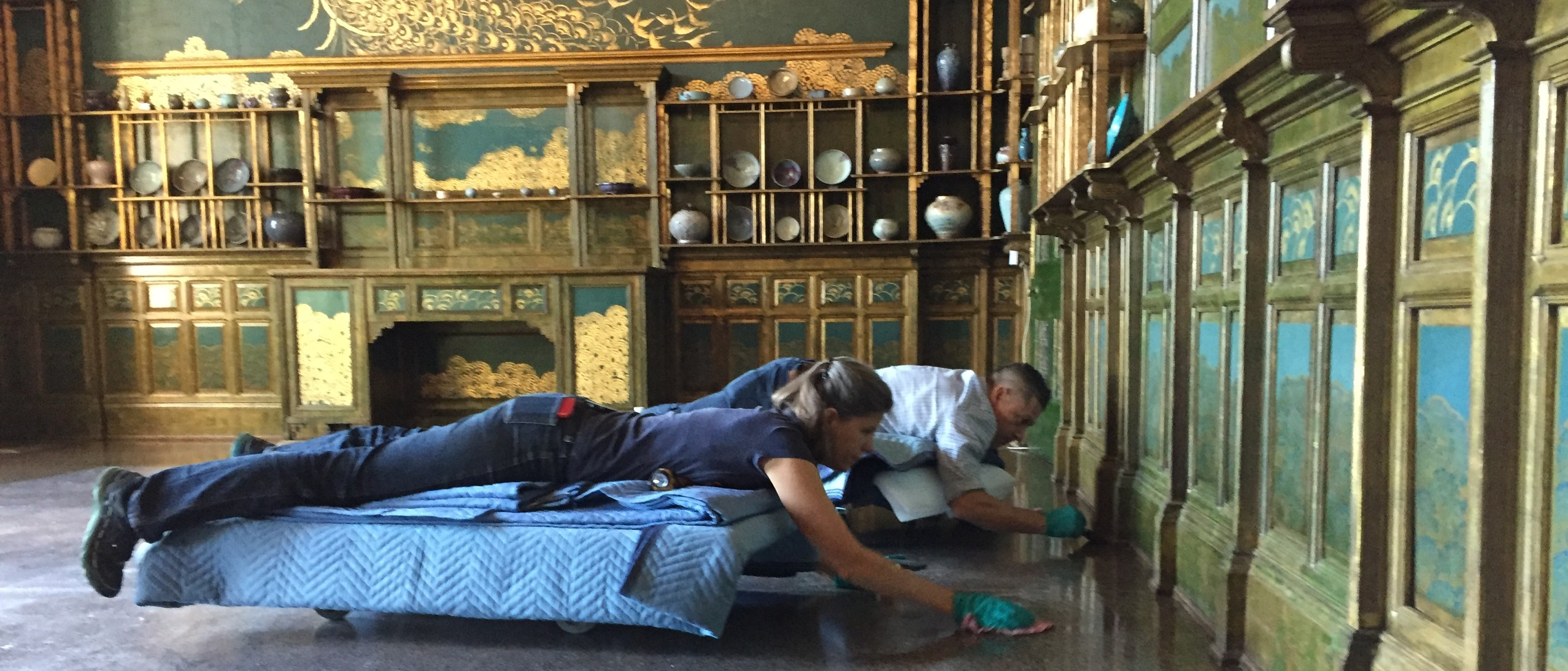 two conservators lying on padding rollers on the floor touches up gilded floorboards in the peacock room
