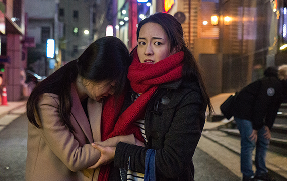 Two girls, in winter attire, are together in a city alley. One girl is crying into the other's shoulder, while the other girl's face is full of fear.