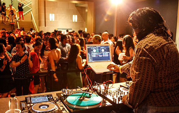 A long-haired man is DJ'ing a dance party.