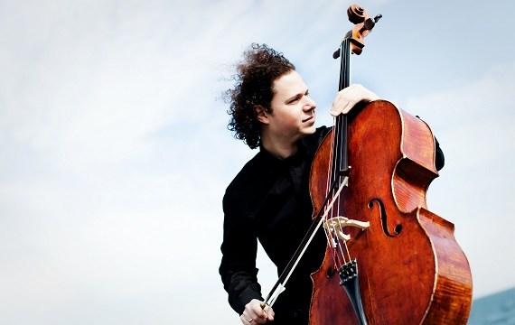 A man with curly hair in black clothes is outside with his cello. The wind is blowing in his hair.