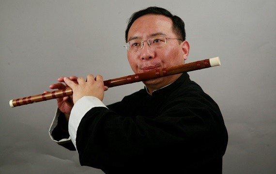 An Asian man with glasses and a black robe is playing a brown flute/dizi.