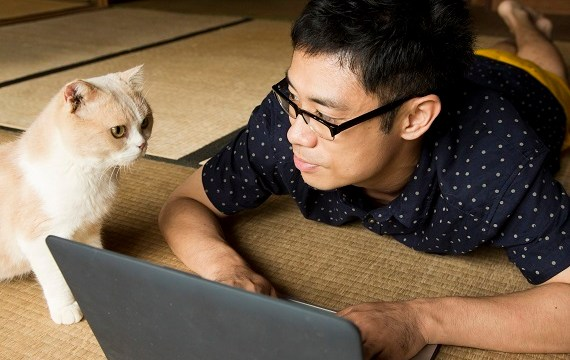 A man is using his laptop on his carpeted floor, looking at his cat.